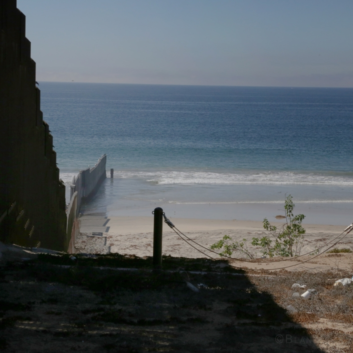 Older Mexico-US border wall view into Pacific Ocean, California side.