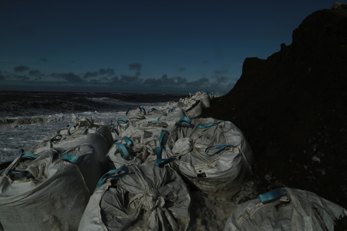 Artist looks out over super bags (gravel bags to protect coastal surges and storms) climate created Arctic Ocean Storm, Utqiagvik, AK